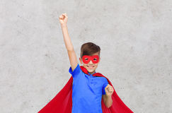 Boy in red superhero cape and mask showing fists Stock Image