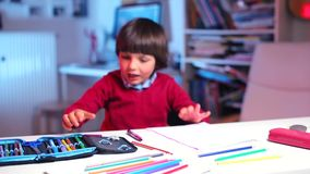 The boy runs to the table, takes a pen in his hand in classroom. A boy in a red sweater runs up to the table, picks up a pen in his hand, looks at the pencil stock footage