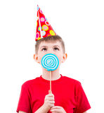 Boy in red t-shirt eating colored candy. Stock Photo