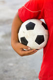 Boy with red t-shirt holding dirty black white football or socce Stock Photography