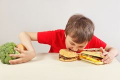 Boy in red at the table chooses between fastfood and vegetable and fruits on white background stock photography