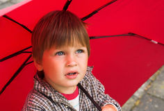 Boy with the red umbrella Stock Image