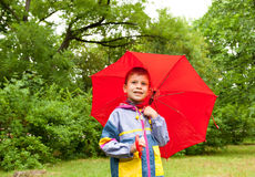 Boy with red umbrella Stock Images