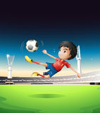A boy in a red uniform at the soccer field Stock Photo