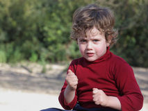 Boy in a Red Waistcoat. Blond boy with curly hair wearing a red vest in the field stock photo