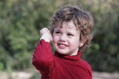 Boy in a Red Waistcoat. Blond boy with curly hair wearing a red vest in the field royalty free stock images
