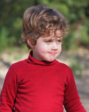 Boy in a Red Waistcoat. Blond boy with curly hair wearing a red vest in the field royalty free stock image