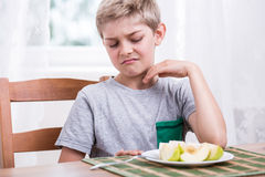 Boy refusing to eat apple. Blonde boy refusing to eat healthy apple Stock Image