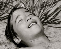 A boy relaxes at the beach. Portrait of a young boy relaxing on the warm sand to dry up Stock Photography