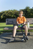 Boy relaxes at a bench from riding push scooter Stock Photos