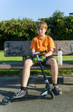 Boy relaxes at a bench from riding push scooter Royalty Free Stock Images