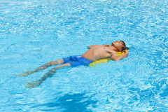 Boy relaxes on his boogie board in the pool Stock Images