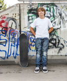 Boy relaxes with his skate board at the skate park Royalty Free Stock Images