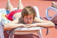 Boy relaxes on a sun lounger Stock Photography