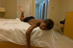 Boy relaxing on bed in hotel room Stock Photography