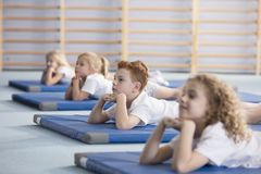 Boy relaxing on blue mat. Boy relaxing on a blue mat with friends in a primary school Royalty Free Stock Images