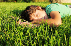 Boy relaxing on grass. Teenager boy relaxing on green grass lawn Stock Photo