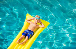 Boy Relaxing and Having Fun in Swimming Pool on Yellow Raft Stock Photo