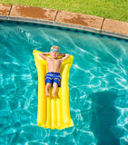 Boy Relaxing and Having Fun in Swimming Pool on Yellow Raft Royalty Free Stock Photography
