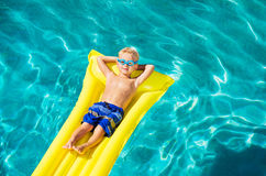 Boy Relaxing and Having Fun in Swimming Pool on Yellow Raft royalty free stock images