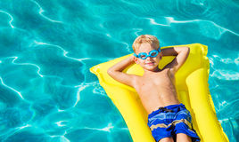 Boy Relaxing and Having Fun in Swimming Pool on Yellow Raft Royalty Free Stock Photos