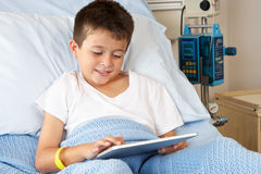 Boy Relaxing In Hospital Bed With Digital Tablet. Smiling Royalty Free Stock Image