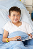 Boy Relaxing In Hospital Bed With Digital Tablet. Smiling Stock Photos