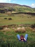 Boy Relaxing in Irish Field. A young boy relaxes in an Irish Field Stock Photos