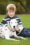Boy Relaxing Outdoors With Pet Dog Royalty Free Stock Photo