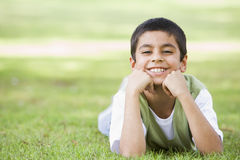 Boy relaxing in park. Looking to camera Royalty Free Stock Image