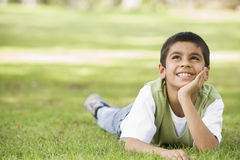Boy relaxing in park. Looking thoughtful Stock Photography