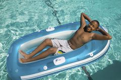 Boy Relaxing in pool Stock Images