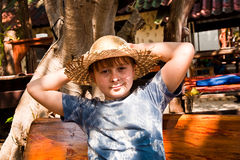 Boy is relaxing, smiling and happy. And has a rest in the sun at an open air restaurant Royalty Free Stock Photography