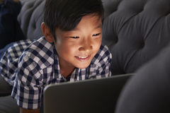 Boy Relaxing On Sofa At Home Using Laptop stock photography