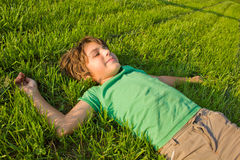Boy relaxing in summer day. Teenager boy relaxing on green grass lawn in summer day Stock Photos