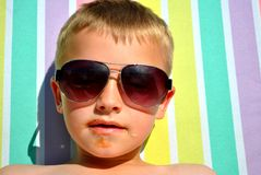 Boy relaxing on the sun bed. Seven-year-old relaxing on the sun bed, in the hot summer day stock photography
