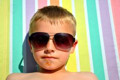 Boy relaxing on the sun bed. Seven-year-old relaxing on the sun bed, in the hot summer day stock photo