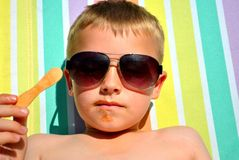 Boy relaxing on the sun bed. Seven-year-old relaxing on the sun bed, in the hot summer day stock photos