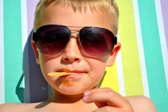Boy relaxing on the sun bed. Seven-year-old relaxing on the sun bed, in the hot summer day stock image