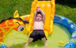 Boy relaxing in the sun on his inflatable pool Royalty Free Stock Photo