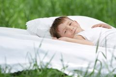Boy relaxing on white bed on natural background Royalty Free Stock Photography