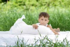 Boy relaxing on white bed on natural background Stock Image