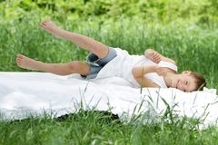 Boy relaxing on white bed on natural background Stock Photography