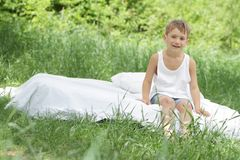 Boy relaxing on white bed on natural background Stock Photo