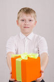 The boy reluctantly giving a gift. Portrait of a teenager with a gift of twelve in the hands of Stock Image