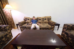 Boy with remote control sitting at sofa in room Stock Images