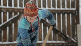 Boy removes snow shovel near the house. Cleaning snow in the winter near the house. stock footage