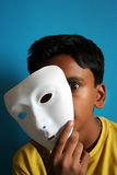 Boy removing the mask. A boy with removing mask with scary eyes stock images