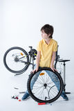 Boy repairing bicycle tire in studio on white Royalty Free Stock Photo