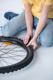 Boy repairing bicycle tire in studio on white Stock Images